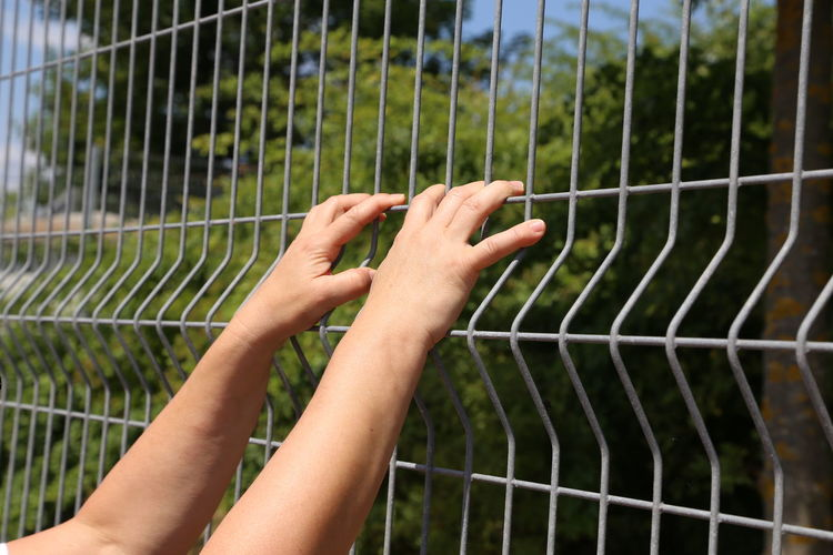 Close-up of hands on metallic fence