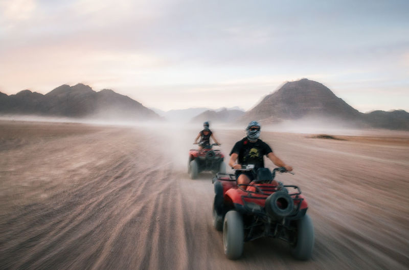 Friends Riding Quadbikes At Desert Against Sky During Sunset