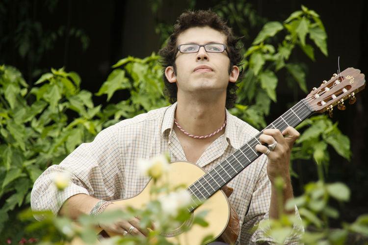 Man playing guitar while sitting at park