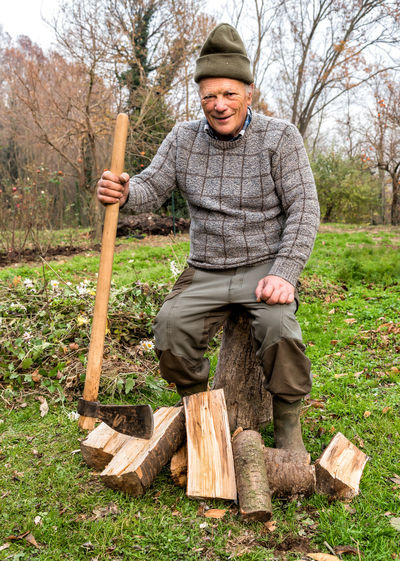 Portrait of smiling senior man with axe sitting on tree stump at field