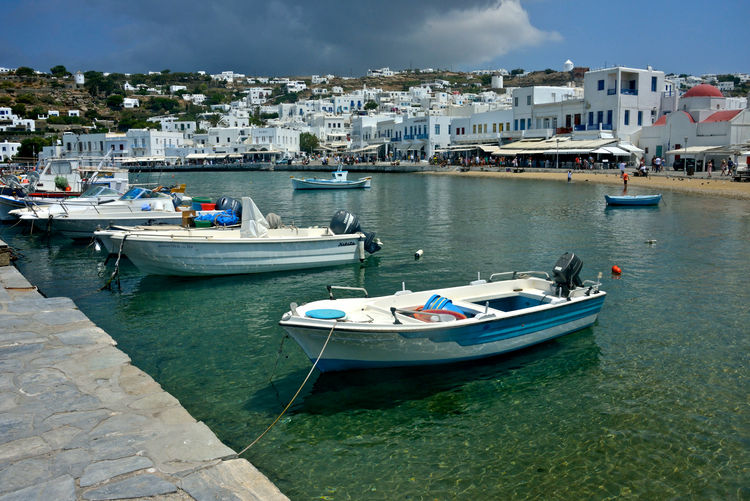 panoramic view of port of Mykonos with boats moored and cityscape behind with white buildings Nautical Vessel Water Building Exterior Mode Of Transportation Transportation Architecture Built Structure Moored City Day Nature Harbor No People Cloud - Sky Sea Building Outdoors Sky Residential District Yacht Canal Marina Fishing Boat Boat Port Chora Mykonos,Greece Summertime Panorama Cityscape Travel Destinations Seafront