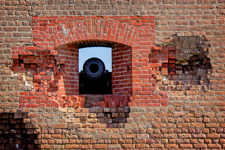 Cannon in the Window Big Gun Architecture Brick Brick Wall Building Building Exterior Built Structure Canon Day No People Outdoors Pattern Protection Red Solid Sunlight Wall Wall - Building Feature War Window