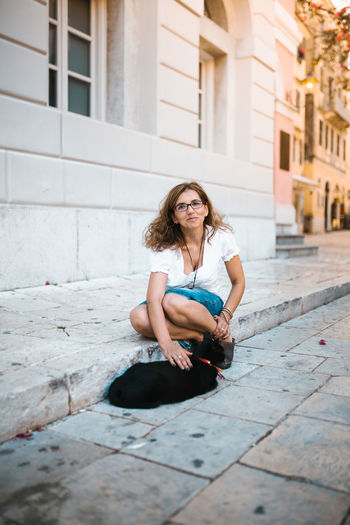 Full length portrait of woman stroking cat on footpath in city
