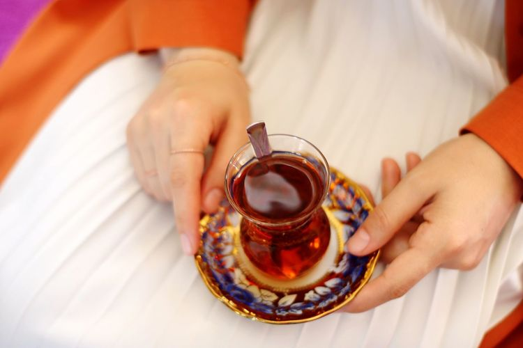 Midsection of woman having herbal tea at home