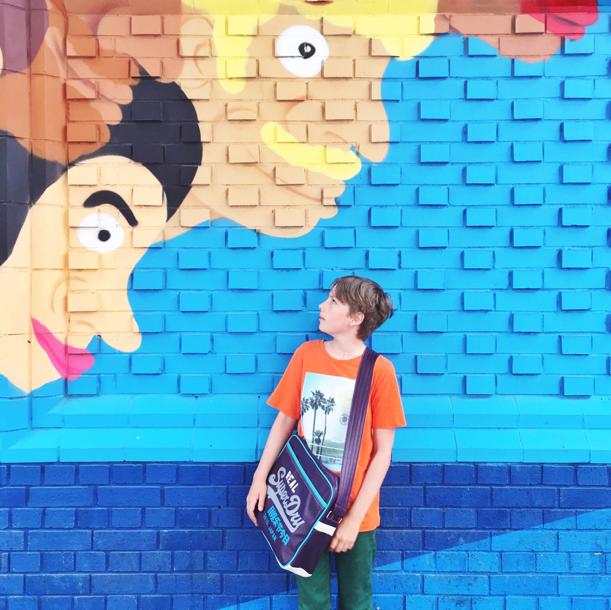 wall - building feature, lifestyles, casual clothing, leisure activity, blue, multi colored, art, brick wall, day, outdoors, portrait, fun