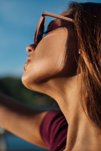 Tanned girl with glasses Tanned Beautiful Woman Beauty Body Part Brown Hair Close-up Day Focus On Foreground Hair Hairstyle Headshot Human Body Part Human Face Human Hair Leisure Activity Lifestyles One Person Portrait Real People Sunlight Women Young Adult Young Women