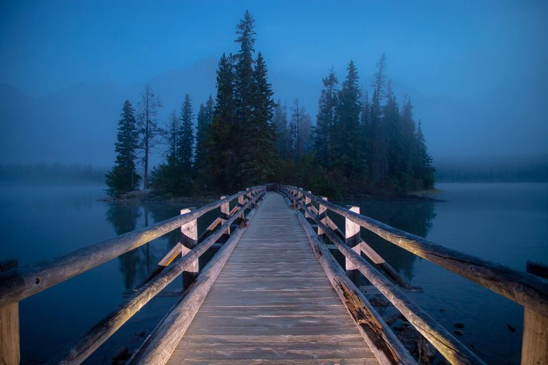 Empty pier over lake at dusk
