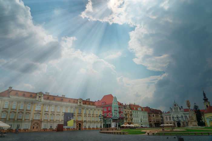 When the Sun Comes Architecture Blue Building Exterior Built Structure Cityscape Cloud - Sky Clouds And Sky Colorful Buildings Day History No People Outdoors Romania Sky Spirituality Sun Sun Rays Sunlight Surreal Timisoara Travel Travel Destinations Travel Photography Wanderlust White