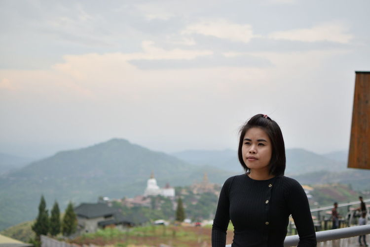 Thoughtful young woman standing on mountain against sky