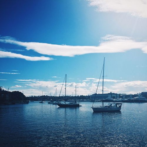 Sailboats in harbor against blue sky