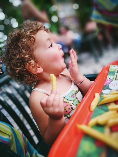 Close-Up Of Boy Eating Fries At Table