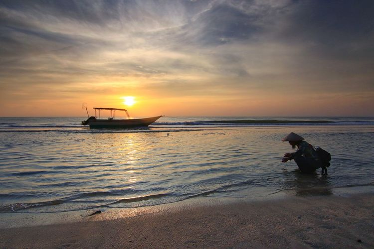 A fisherman and fishing boat at the beach with nice sunrise Nautical Vessel Sea Sunset Beach Low Tide Beauty Sand Silhouette Sun Tide Seascape Fishing Boat Romantic Sky Wave