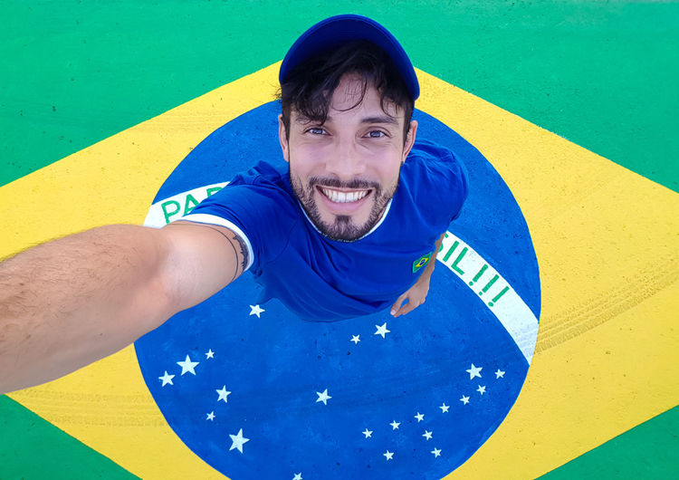 Directly Above Portrait Of Man Smiling While Standing On Brazilian Flag