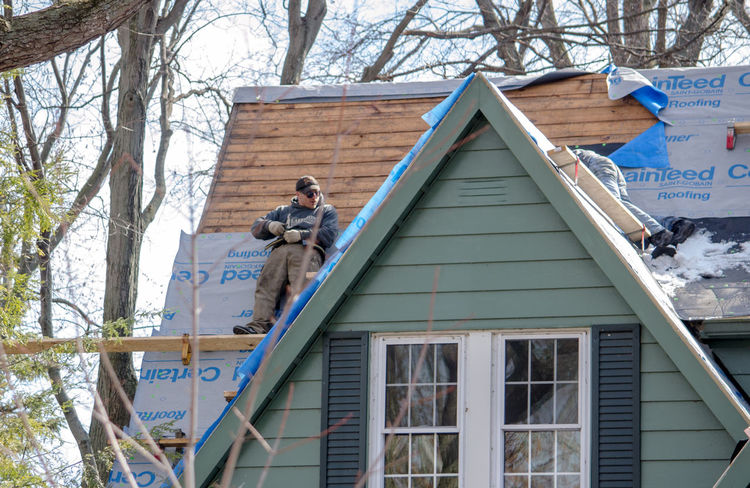 March 2018 Michigan USA; workers put a new roof on a home with a very steep grade on a cold winters day Construction Home Houses Repairs Roof Replacement Sunnyvale Work Adult Architecture Building Building Exterior Built Structure Day Hard Workers House Job Men Outdoors Outdoors Photograpghy  People Roof Repair Roofers Shingles Trade Tree