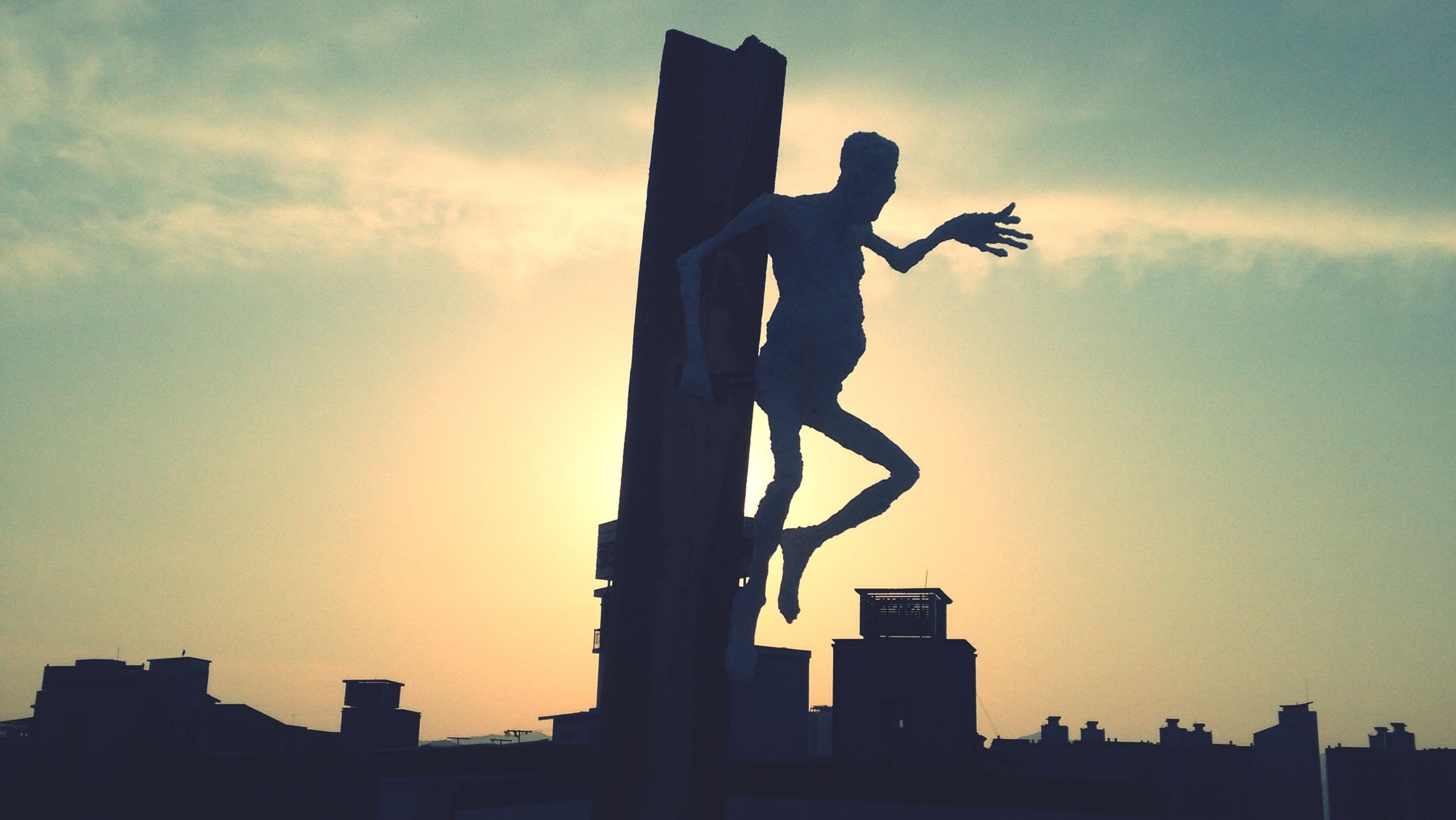statue, sculpture, human representation, silhouette, low angle view, art, art and craft, creativity, sunset, sky, architecture, built structure, building exterior, outdoors, city, animal representation, dusk, no people