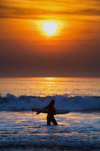 surfer enjoys dramatic sunset during the November 2018 fires in California. Surfing, Surf, Waves, Surfboard, Females, Sunset California, USA Beach Outdoors Ocean Water Summer San Francisco