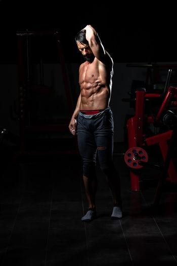 Full length of shirtless man standing against black background