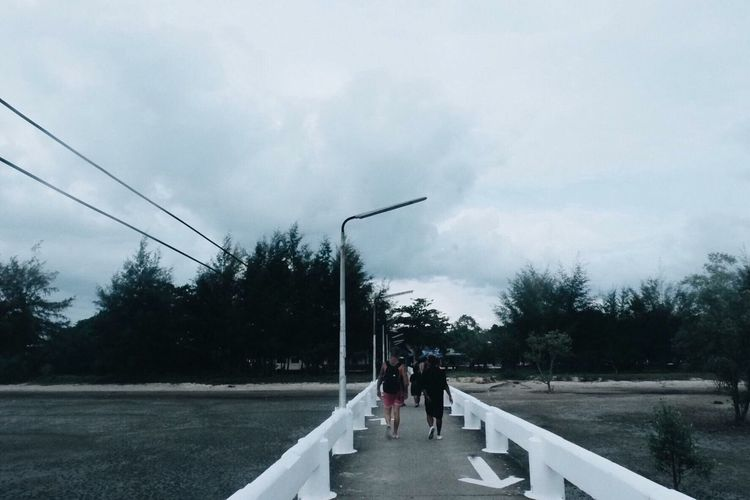 People walking on road against sky