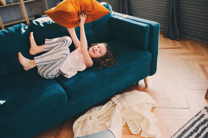 kid girl playing at home in lazy weekend morning, pillow fight on cozy couch in pajama in scandinavian interior Fun Kids Life Moment Morning Weekend Boys Candid Childhood Cozy Day Elementary Age Full Length Girls Hardwood Floor High Angle View Home Interior Indoors  Leisure Activity Lifestyles Pajamas People Pillow Playing Real People