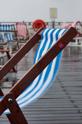 Close-up of deck chair on pier