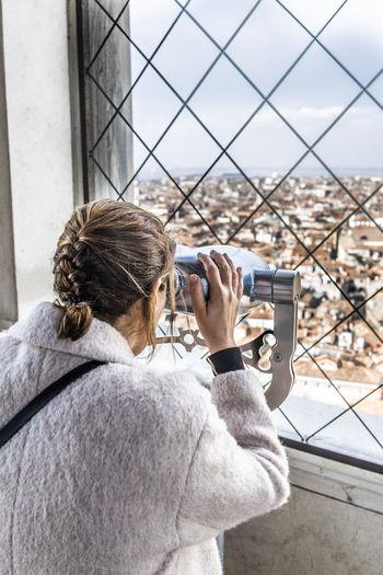 Woman looking city through binoculars