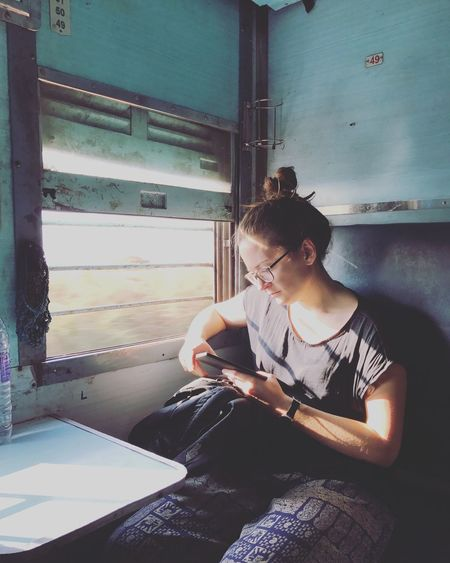 Young Woman Using Digital Tablet While Traveling In Train