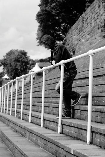 Full length side view of thoughtful man leaning on railing while standing on steps