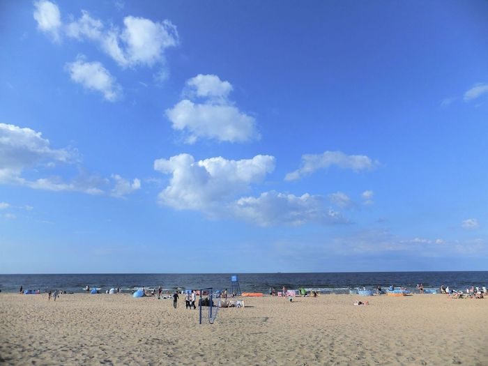People On Beach Against Blue Sky
