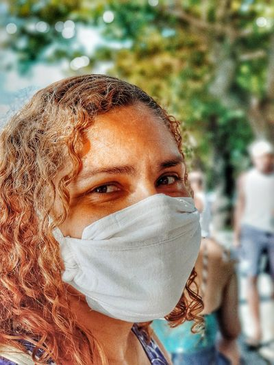 Close-up portrait of woman wearing mask standing outdoors