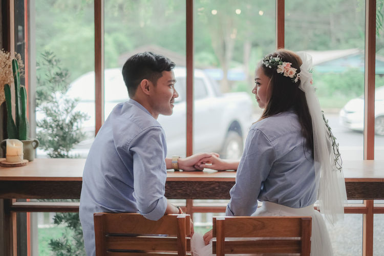 Side view of young couple sitting on table