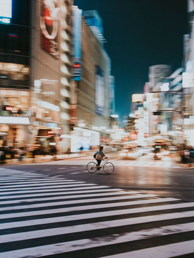 Blurred motion of people riding bicycle on road in city