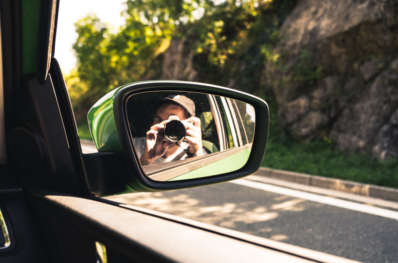 Man Reflecting On Side-View Car Mirror While Photographing With Digital Camera