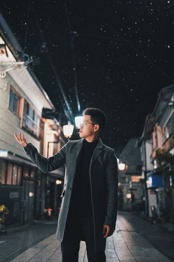 Young man standing in city at night