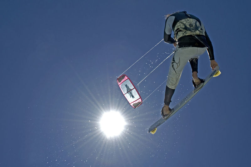 Blue Board Building Clear Sky Drops Funsport Jumping Jumps Kiteboarding Kites Kitesurfing Lines Outdoors Red Sea Reflection Sea Sky Sport Suit Sun Water Wave Wetsuit Windy Winter
