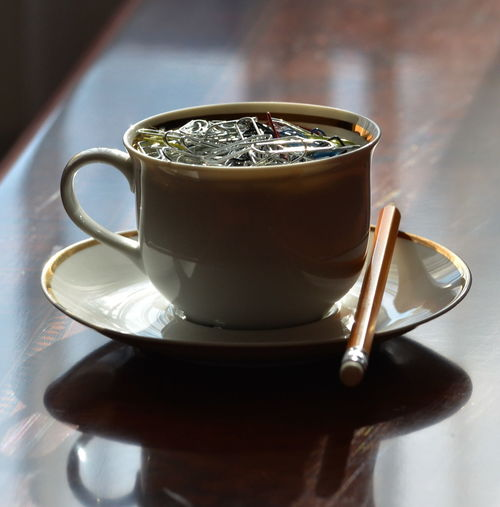 Close-up of paper clips in cup on table