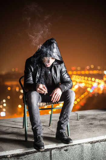 Chair Cigarettes City Life Illuminated Jacket Leisure Activity Lifestyles Night Lights Orange Color Outdoors Rooftop Smoking Traffic