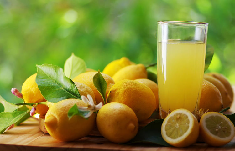 lemons, flowers and juice cup on table Citrus Fruit Close-up Drink Drinking Glass Food Food And Drink Freshness Fruit Glass Healthy Eating Leaf Lemon Refreshment Table