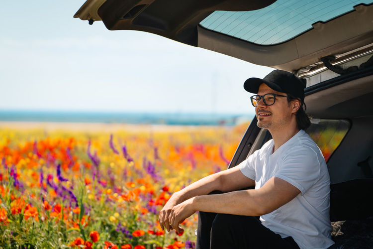Young man wearing sunglasses standing on street amidst flowering plants