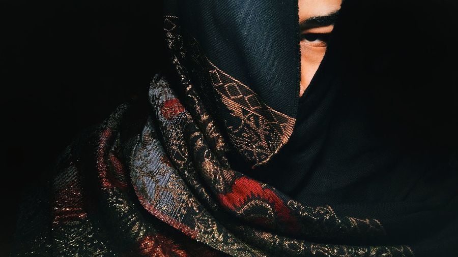 Close-up of woman against black background