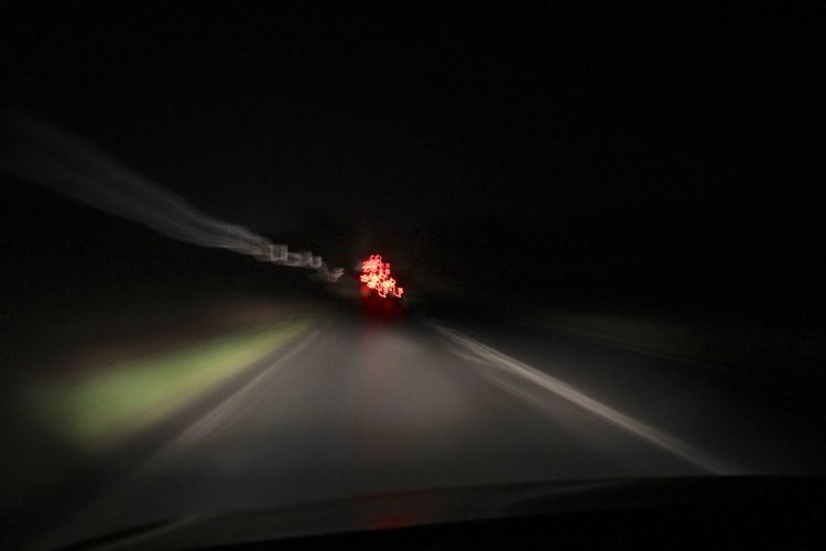 Illuminated car on road against sky at night