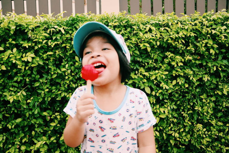 Cute girl eating candy against plants