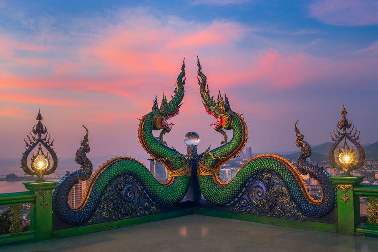 Statue against illuminated building against sky