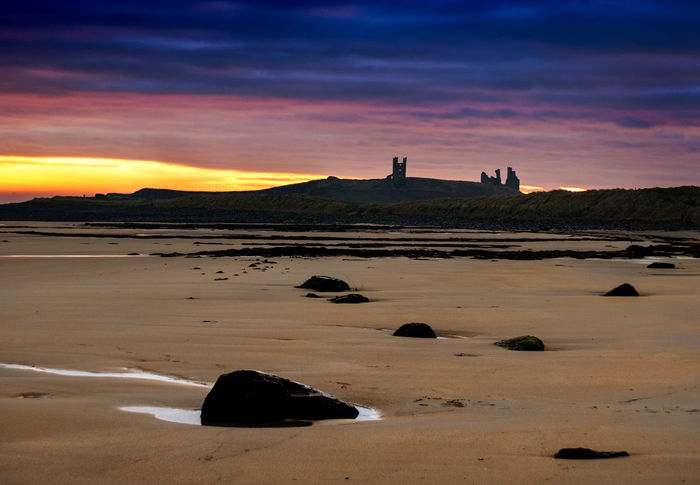 View to the castle Dunstanburgh Castle Architecture Beauty In Nature Building Exterior Built Structure Castle Ruin Cloud - Sky Day Lighthouse Nature No People Outdoors Sand Scenics Sky Sunset Tranquility Travel Destinations Water