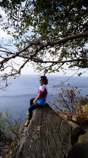 Woman sitting on rock by tree