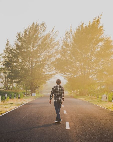 Rear angle view of young boy skateboarding on country road at sunset