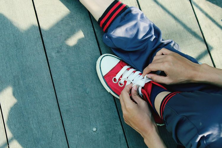 Low Section Of Person Tying Shoelace On Floorboard