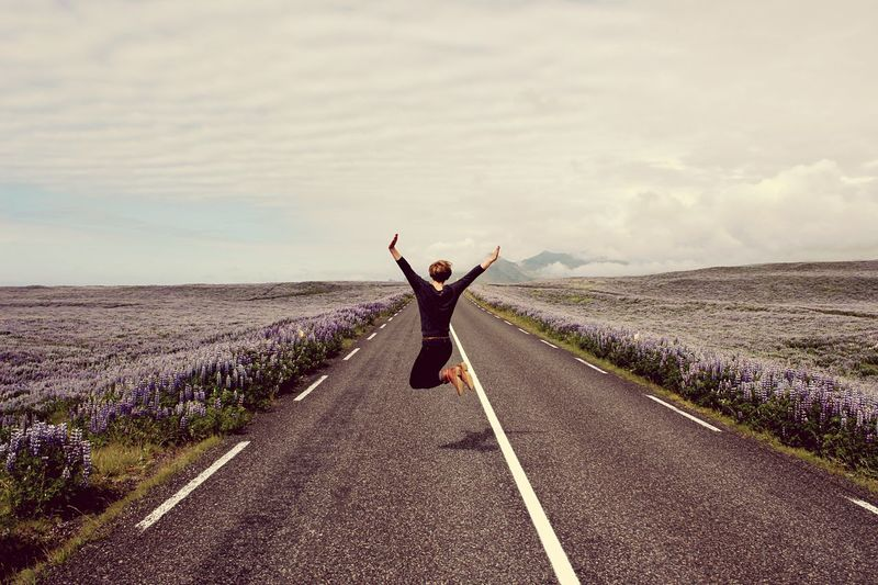 Woman jumping on road amidst flowering field against sky