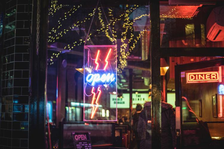 Illuminated open sign on restaurant at night