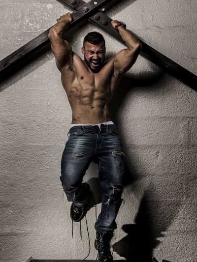 Muscular Man Holding on to steel girdles against a concrete wall screaming Abdominal Abs Adult Adults Only Agressive Look Beautiful People Beauty Day Handsome Indoors  Lifestyles Men One Man Only One Person One Young Man Only Only Men People Screaming Shirtless Sixpacks Young Adult Young Men