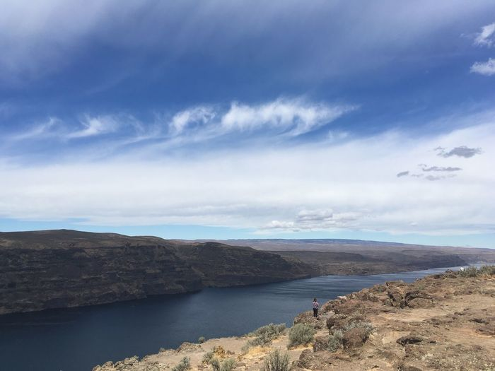 Rear view of woman standing on cliff by columbia river against sky